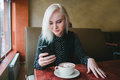 Young beautiful blond girl looks into the phone sitting in a cafe. Coffee with marshmallows for breakfast. Royalty Free Stock Photo