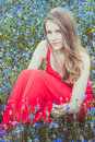 Young beautiful blond girl sitting in red dress in cornflower field Royalty Free Stock Photo