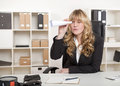 Young beautiful blond haired business woman bored businesswoman sitting at her desk in the office playing with a paper telescope Stock Photography