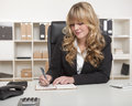 Young beautiful blond haired business woman businesswoman writing notes at her desk as she sits in her office with shelving lined Stock Images