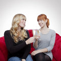 Young beautiful blond and red haired girls with champagne on red Stock Photo