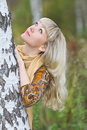 Young, beautiful blond woman stand near a birch Royalty Free Stock Image