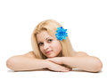 Young beautiful blonde girl with blue flower in hair on white background Stock Photos