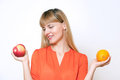Young beautiful blonde girl choosing between apple and orange. Royalty Free Stock Image