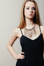 Young beautiful blonde woman with black dress and a great necklace Royalty Free Stock Photography