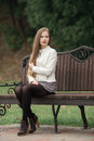 Young beautiful blonde woman with extra long straight hair bright red lipstick corrects hairstyle posing on park bench Royalty Free Stock Photo