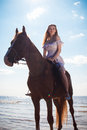 Young beautiful blonde woman and a horse near sea Stock Photo