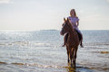 Young beautiful blonde woman and a horse near sea Stock Image