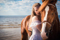 Young beautiful blonde woman and a horse near sea Royalty Free Stock Image