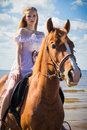 Young beautiful blonde woman and a horse near sea Royalty Free Stock Photos