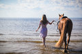 Young beautiful blonde woman and a horse near sea Stock Photography