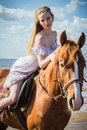 Young beautiful blonde woman and a horse near sea Royalty Free Stock Images