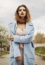 Young beautiful blonde woman posing in blue coat outdoors