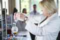 Young beautiful blonde woman researcher chemist preparing substances for chemical use with laboratory dishes.Pharmacist making ch Royalty Free Stock Photo
