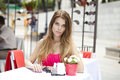 Young beautiful blonde woman sitting in a summer restaurant girl Royalty Free Stock Images