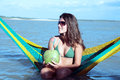 Young beautiful brazilian woman drinking coconut milk smiling bikini dressed and holding fresh juice in the tatajuba lagoon in Royalty Free Stock Images
