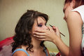 Young beautiful bride applying wedding make up by artist Royalty Free Stock Photography