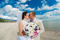 Young and beautiful bride and groom on the beach in summer Royalty Free Stock Images