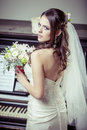 Young beautiful bride holding bouquet of flowers vintage light tonned style Stock Photo