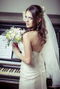 Young beautiful bride holding bouquet of flowers vintage light tonned style Royalty Free Stock Images