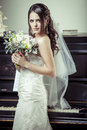 Young beautiful bride holding bouquet of flowers vintage light tonned style Royalty Free Stock Photography