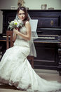 Young beautiful bride holding bouquet of flowers vintage light tonned style Royalty Free Stock Image