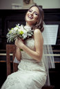 Young beautiful bride holding bouquet of flowers vintage light tonned style Stock Photos
