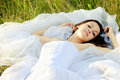 Young beautiful bride lying in green grass Royalty Free Stock Photography