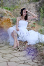 Young beautiful bride sitting in desert Stock Photo