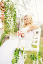 Young and beautiful bride sitting on a white swing in a spring g Royalty Free Stock Photo