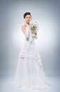 Young and beautiful bride standing with the flower bouquet Stock Image