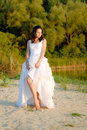 Young beautiful bride standing by river thoughtful Royalty Free Stock Photo
