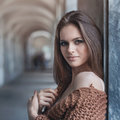 Young beautiful brunette in fashionable clothes near the wall Royalty Free Stock Photo