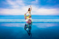 Young beautiful brunette girl in a white swimsuit with a waving skirt is next to the infinity pool. Tropical sea in the background Royalty Free Stock Photo