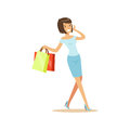 Young beautiful brunette woman in an elegant clothes walking with shopping bags and talking on mobile phone colorful Royalty Free Stock Photo