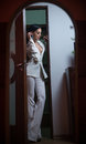 Young beautiful brunette woman in elegant white suit with trousers standing in door frame. Seductive dark hair girl posing indoors Royalty Free Stock Photo