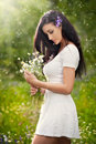 Young beautiful brunette woman holding a wild flowers bouquet in a sunny day. Portrait of attractive long hair female in white Royalty Free Stock Photo