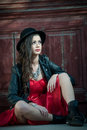 Young beautiful brunette woman with red short dress and black hat posing sensual in vintage scenery. Romantic mysterious lady Royalty Free Stock Photo