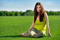 Young beautiful brunette woman sitting on green meadow portrait of with long hair wearing bright dress grass at summer Stock Images