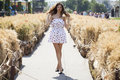 Young beautiful brunette woman in white dress walking on the str Royalty Free Stock Photo