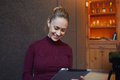 Young beautiful businesswoman browsing internet via touch pad during coffee break in restaurant
