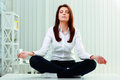 Young beautiful businesswoman meditates on the table in office Stock Image