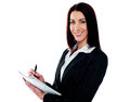 Young beautiful businesswoman writing on clipboard Royalty Free Stock Images