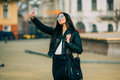 Young beautiful casual girl takes a selfie on her cell phone with sunglasses in jacket an black bag smile to camera spring city Royalty Free Stock Photos