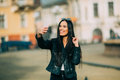 Young beautiful casual girl takes a selfie on her cell phone with sunglasses in jacket an black bag smile to camera spring city Stock Photo