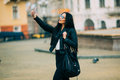 Young beautiful casual girl takes a selfie on her cell phone with sunglasses in jacket an black bag smile to camera spring city Royalty Free Stock Images