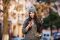 Young beautiful casual girl texting on her cell phone on spring city street calling in jacket and hat smile look Stock Photo