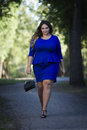 Young beautiful caucasian plus size fashion model in blue dress outdoors, xxl woman on nature Royalty Free Stock Photo