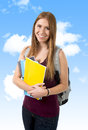 Young beautiful college student girl carrying backpack and books under blue sky posing happy confident in university education Stock Photos