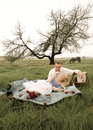 Young beautiful couple enjoying a picnic in field with horse and tree background Royalty Free Stock Images